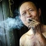 Man smoking in Dehang. China travel photography. Photo by New York freelance travel photographer Jocelyn Voo.
