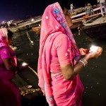 India photography. Woman releasing candle into Ganges river.
