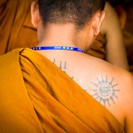 India photography. Tattooed monk praying.