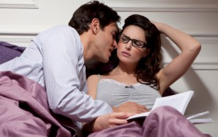 woman working in bed ignoring man